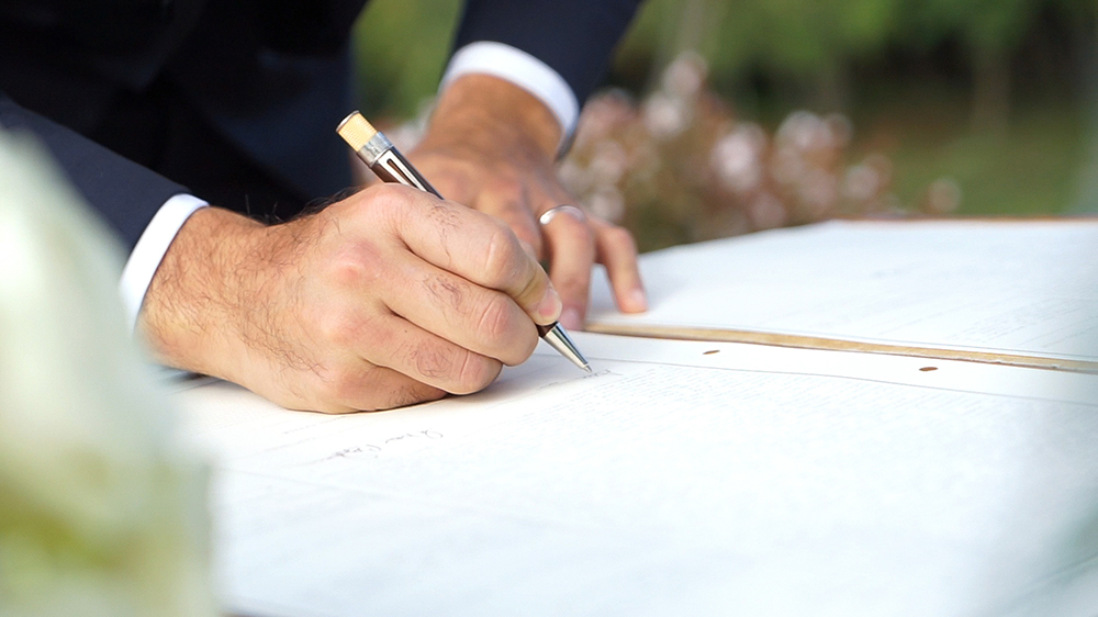 Mann unterschreibt Ehevertrag