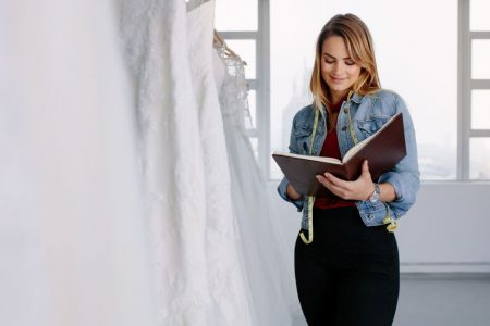 Female tailor writing in a diary while standing wedding dress store. Female dress designer working in bridal clothing store.